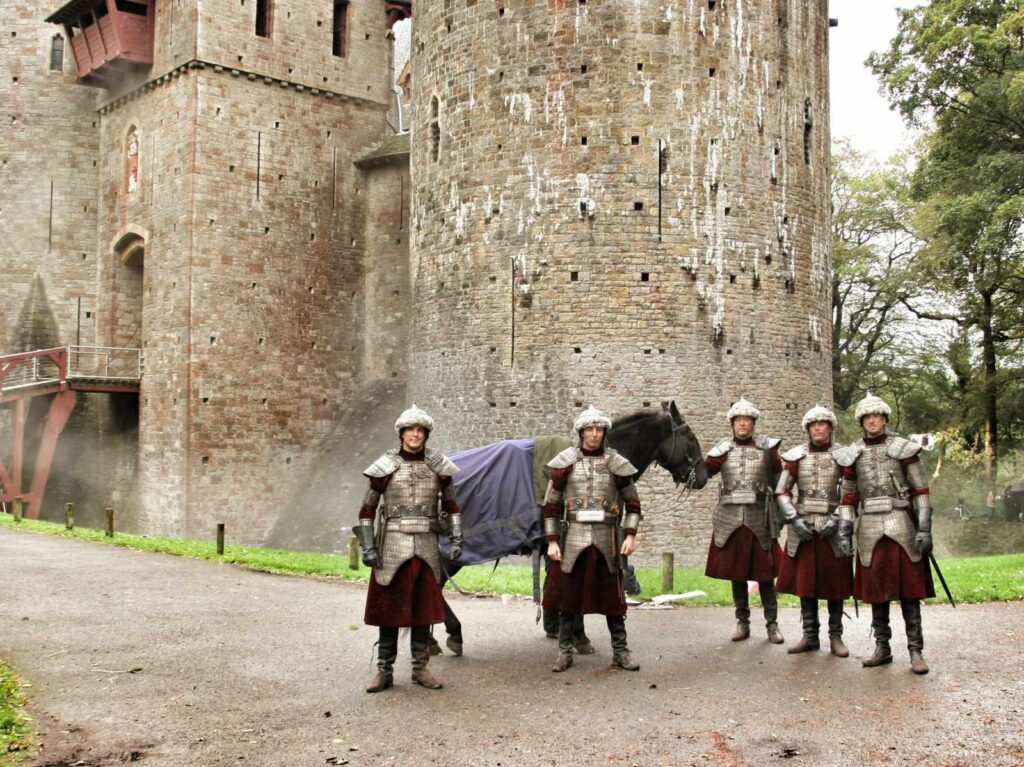 Actors dressed as soldiers on a TV filming set with Castell Coch in the background