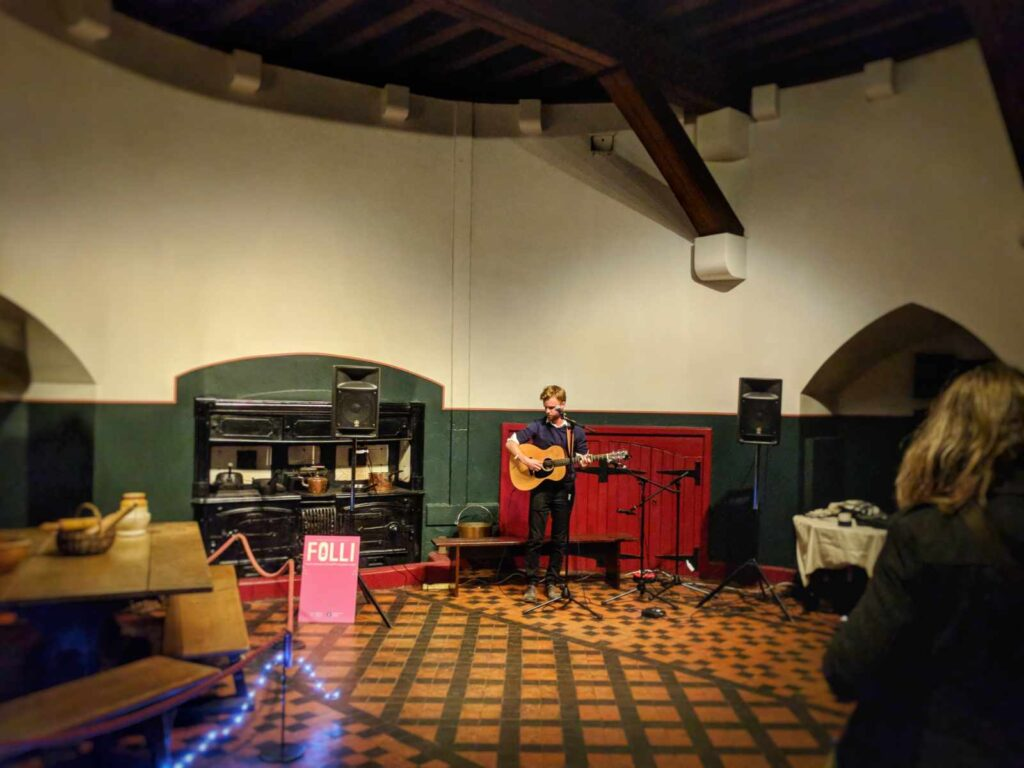 Acoustic guitarist in kitchen at Castell Coch