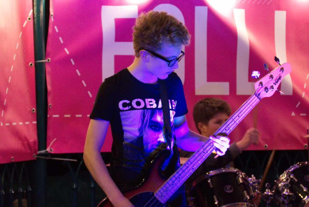 Guitarist with drummer in background