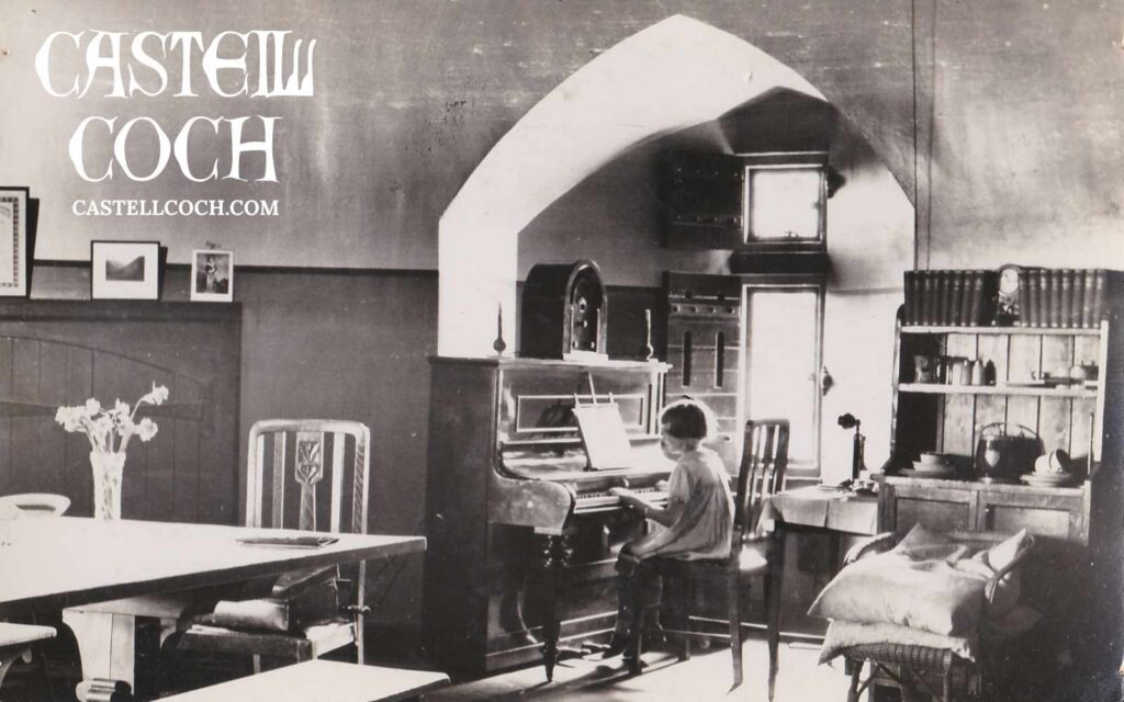 Postcard featuring a photo of a girl playing piano in the kitchen of Castell Coch